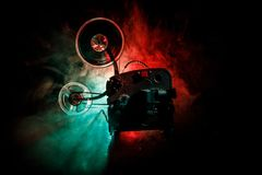 Old style movie projector, close-up. Film projector on a wooden background with dramatic lighting and selective focus. Movies and. Old style movie projector Stock Image