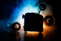 Old style movie projector, close-up. Film projector on a wooden background with dramatic lighting and selective focus. Movies and. Old style movie projector Royalty Free Stock Photos