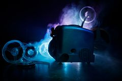 Old style movie projector, close-up. Film projector on a wooden background with dramatic lighting and selective focus. Movies and. Old style movie projector Stock Images