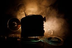 Old style movie projector, close-up. Film projector on a wooden background with dramatic lighting and selective focus. Movies and. Old style movie projector Royalty Free Stock Images