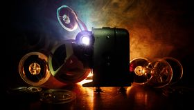 Old style movie projector, close-up. Film projector on a wooden background with dramatic lighting and selective focus. Movies and. Old style movie projector Stock Photos