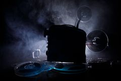 Old style movie projector, close-up. Film projector on a wooden background with dramatic lighting and selective focus. Movies and. Old style movie projector Royalty Free Stock Image