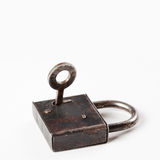 Old style padlock with key in hole. hanging lock close-up. texture and detailed. white background. soft focus Stock Images