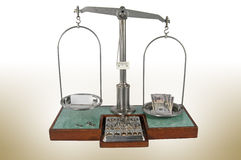 Old style pharmacy scale with money heavier than small box Stock Photos