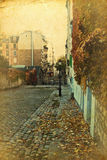 Old style picture of typical old Paris. Old style picture of a typical old Parisian road on the Montmartre hill with autumn leaves, overlaid with an old paper Royalty Free Stock Photos