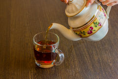 Old-style porcelain kettle pouring tea from jug to cup of tea stock photos