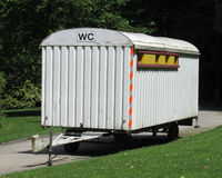 Old Style Portable Toilet. An old fashioned wood constructed portable toilet block mounted on a trailer in an outdoors setting Stock Image