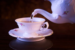 Old-style pouring tea to cup on black background Stock Photography