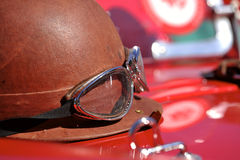 Old style race helmet on racing car. An old style race helmet on a red racing car Stock Photos
