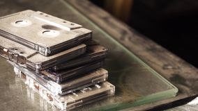 Old style retro tapes with dust over it. Old style vintage retro cassette tapes lying at dusted background stock footage
