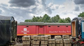Old style Royal Mail mobile sorting office seen on railway siding, framed by two sleeper cars. This old style Royal Mail sorting office shows detail of the red Stock Photos