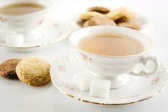 Old-style shot of cup of tea with cookies on white Royalty Free Stock Photos