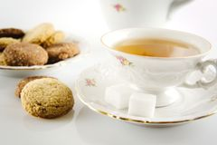 Old-style shot kettle with cup of tea with cookies foreground on Royalty Free Stock Photo