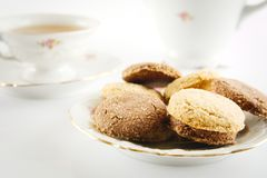 Old-style shot kettle with cup of tea with cookies foreground on Royalty Free Stock Photography