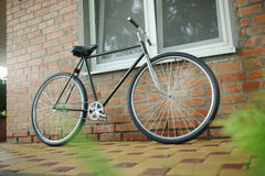 Old style singlespeed bicycle against brick wall royalty free stock images