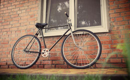 Old style singlespeed bicycle against brick wall stock images