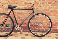Old style singlespeed bicycle against brick wall Stock Photo