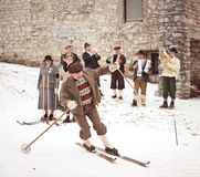 Old-style skiing performance in Slovenia. SKOFJA LOKA, SLOVENIA - JANUARY 3: Rovtarji skiers in traditional retro style costumes, with old wooden ski gear skiing Royalty Free Stock Image
