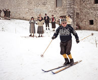 Old-style skiing performance in Slovenia. SKOFJA LOKA, SLOVENIA - JANUARY 3: Rovtarji skiers in traditional retro style costumes, with old wooden ski gear skiing Royalty Free Stock Images