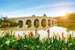 Old arch bridge on the lake in China. Old style stone Chinese arch bridge in a green garden pond in Beijing, China Royalty Free Stock Photo