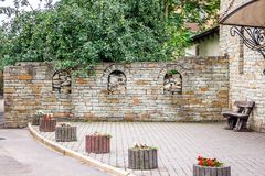An old-style stone fence near a building in a modern city_ Stock Images
