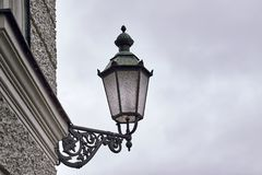 Old style street light. Attached to a wall. Moody weather. Copy space Royalty Free Stock Images