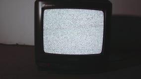 Old style television set static screen on floor in dark room flashing light. Old style black plastic television set white static noise screen on floor in dark stock video