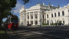 Old style tram passing by Burgtheater. VIENNA, AUSTRIA - AUGUST 2016: Old style red tram passing by Burgtheater, the Austrian National Theatre stock video