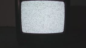 Old style TV set static screen on floor in dark room flashing light. Old style black plastic TV set, camera flying into white static noise screen on floor in stock video