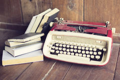 Old style typewriter with books on wooden floor Stock Photo