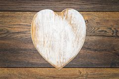 Retro classic Valentine`s Day cad, large white painted wooden hart isolated and in center on vintage oak panels - top view stock images