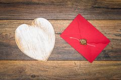 Retro classic Valentine`s Day cad, large white painted wooden hart, isolated, red envelope with wax seal, on vintage oak panels - royalty free stock image