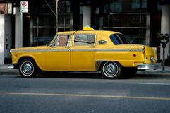 Old Style Vintage Taxi. An old style vintage yellow taxi on a city street royalty free stock image