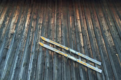 Old style vintage wooden skis with strap binding hanging on rust Stock Images
