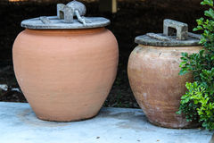 Old style water jar. Made of clay and wood cover and coconut shell ladle Stock Photos