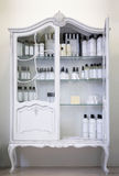Old style, white baroque cabinet with bottles. Antique cupboard with glass shelf, and perfume ingredients inside Stock Photography