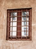 Old window with black metal bars. Old style window with dirty glasses and antique rusty grate with black metal bars, and red house wall Stock Photos