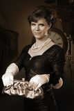 Old style woman picture with purse. Old style woman holding purse with clock in background Stock Photography
