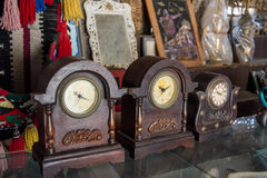 Old style wooden clocks. On the shelf in souvenirs shop Royalty Free Stock Photography
