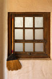 Old styled broom stick hanging by the wooden vintage window to k Royalty Free Stock Photos