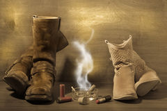 Old styled man and woman boots with cigar cartridg Royalty Free Stock Photos
