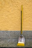 An old styled yellow broom and metal dustpan Stock Photography
