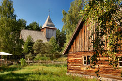 Old stylish cottage with wooden church in the back. Old cottage with wooden church in the back Royalty Free Stock Photo