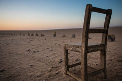 Old, Stylish, Wooden Chair on Beach with sunset Royalty Free Stock Image