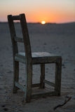 Old, Stylish, Wooden Chair on Beach with sunset Royalty Free Stock Photography