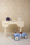 Old stylized interior with white table and old blue car toy Royalty Free Stock Images