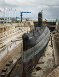 Old submarine surfaced. Shipyard in the port, with old rusty submarine under repair royalty free stock photos