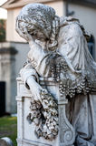 An old suffering woman statue cries on her knees onto the tombstone royalty free stock images