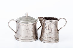 Old sugar bowl with lid and an old coffee pot with spots of rust. On a white background royalty free stock image