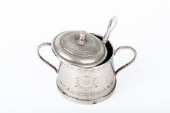 Old sugar bowl with lid and spoon with spots of rust on a white. Background royalty free stock photo